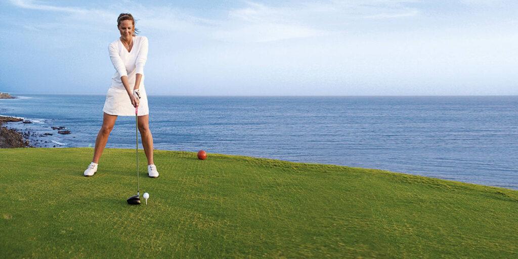 hawaii golf cruise lady golfer on golf green ocean in background